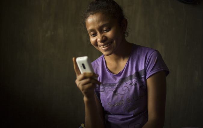 Ela, in Indonesia, looks at her mobile phone.