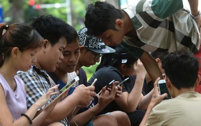 Forbes - People use tablets and smartphones at a public park next to Hoan Kiem Lake in the center of Hanoi on August 10, 2016. (Photo: HOANG DINH NAM/AFP/Getty Images)